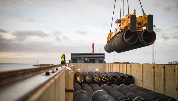 Pipes are loaded onto a vessel in the northern German port of Mukran for transshipment to a storage yard - Sputnik International