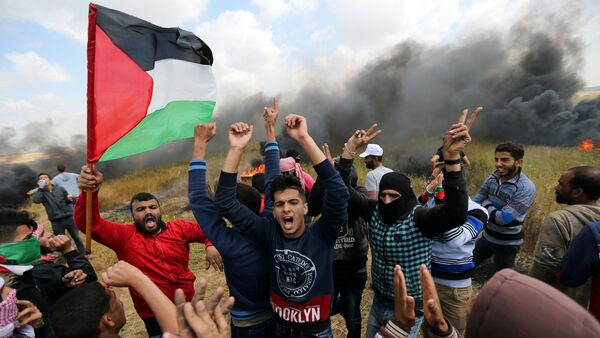 Palestinians shout during clashes with Israeli troops, during a tent city protest along the Israel border with Gaza, demanding the right to return to their homeland, the southern Gaza Strip March 30, 2018. - Sputnik International