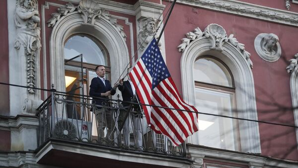 Diplomatic mission personnel remove a US flag from the building of the US Consulate-General on Furshtatskaya Street in St. Petersburg - Sputnik International