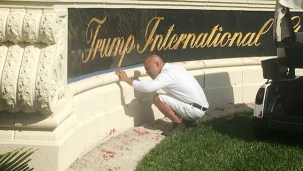 A worker cleans up red paint from the stone sign at the entrance to the Trump International Golf Club in West Palm Beach, Fla., Sunday, April 1, 2018. - Sputnik International