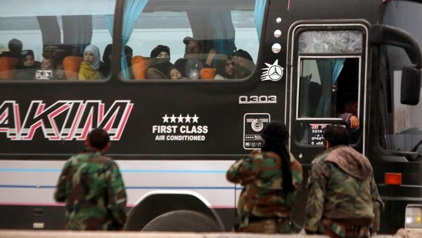 Syrian rebels and civilians look through a bus window as they leave Harasta in eastern Ghouta, in Damascus, Syria March 23, 2018 - Sputnik International