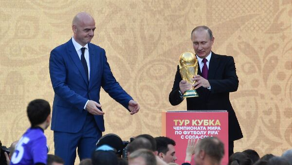 (File) Russian President Vladimir Putin kick starts the FIFA World Cup Trophy Tour at the Grand Sports Arena, which was opened after a reconstruction, during the visit to the Luzhniki Olympic Complex in Moscow. Left: FIFA President Gianni Infantino - Sputnik International