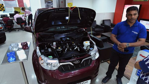 This photo taken on July 21, 2017 shows a sales executive talking about Mahindra's electric car e2o Plus on display at a showroom in New Delhi - Sputnik International