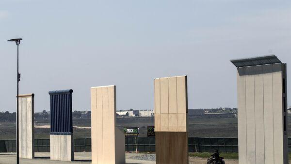 A US border patrol quad is seen next to US President Donald Trump's border wall prototypes from Tijuana, northwestern Mexico - Sputnik International