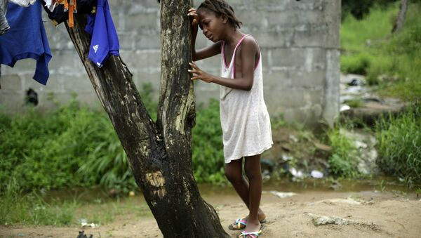 A child cries as community activists approach her outside her home in Liberia, a day after her mother was taken away by an ambulance to an Ebola ward, - Sputnik International