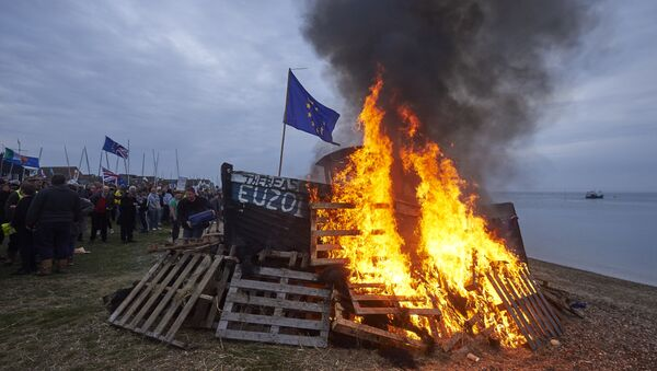 The remains of a small boat flying European flags is burnt on a bonfire during a demonstration in Whitstable, southeast England on April 8, 2018 against the Brexit transition deal that would see Britain continue to adhere to the Common Fisheries Policy after formally leaving the EU - Sputnik International