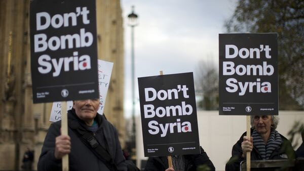 Supporters of the Stop the War Coalition hold placards protesting against Britain launching airstrikes against Islamic State extremists inside Syria, outside the Houses of Parliament as a debate goes on before a vote, Wednesday, Dec. 2, 2015. - Sputnik International