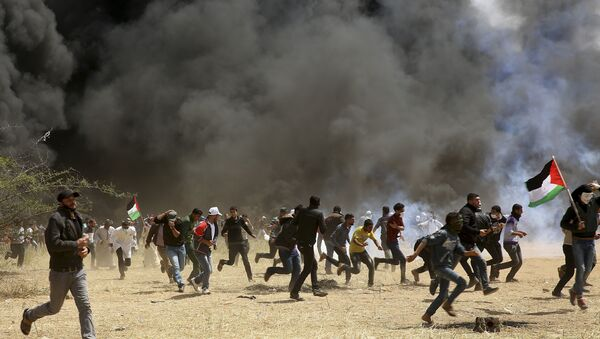 Palestinian protesters run to cover from teargas fired by Israeli soldiers during clashes with Israeli troops along Gaza's border with Israel, east of Khan Younis, Gaza Strip, Friday, April 6, 2018 - Sputnik International