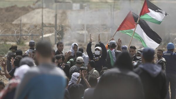 Palestinian protesters chant slogans as they gather during a protest at the Gaza Strip's border with Israel, Friday, April 13, 2018 - Sputnik International