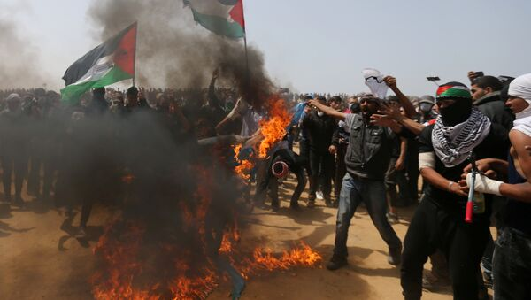 Palestinian demonstrators burn an Israeli flag during a protest demanding the right to return to their homeland, at the Israel-Gaza border, in the southern Gaza Strip, April 13, 2018 - Sputnik International
