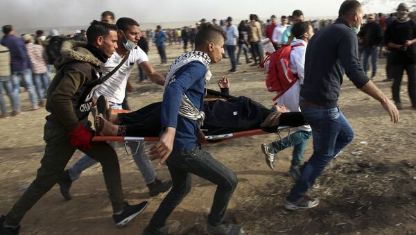 Palestinian protesters evacuate a wounded woman during clashes with Israeli troops along Gaza's border with Israel, Friday, April 13, 2018. - Sputnik International
