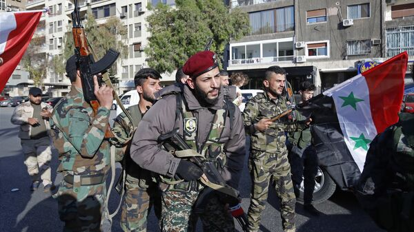 Syrian soldier wave weapons and national flags as they chant slogans against U.S. President Trump during demonstrations following a wave of U.S., British and French military strikes to punish President Bashar Assad for suspected chemical attack against civilians, in Damascus, Syria, Saturday, April 14, 2018 - Sputnik International