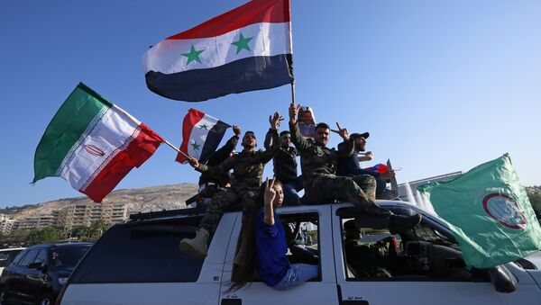 Syrian government supporters wave Syrian, Iranian and Russian flags as they chant slogans against U.S. President Trump during demonstrations following a wave of U.S., British and French military strikes to punish President Bashar Assad for suspected chemical attack against civilians, in Damascus, Syria, Saturday, April 14, 2018 - Sputnik International