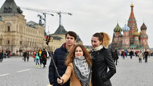 Tourists taking selfie on Red Square, Moscow. In the background St. Basil's Cathedral - Sputnik International