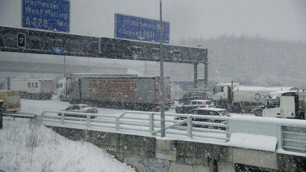 Vehicles crawl along a road as heavy snow falls in south east England - Sputnik International