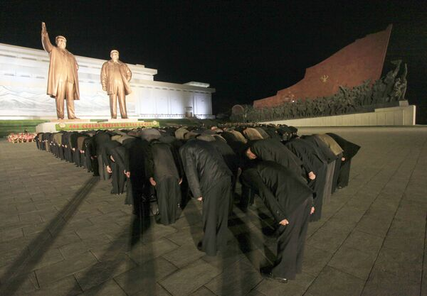 North Koreans bow in front of the statues of late leaders Kim Il Sung and Kim Jong Il on the Mansu Hill. - Sputnik International