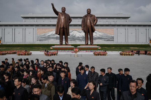 People walk away after paying their respects before the statues of late North Korean leaders Kim Il Sung and Kim Jong Il, at Mansu hill in Pyongyang April 15, 2018. - Sputnik International