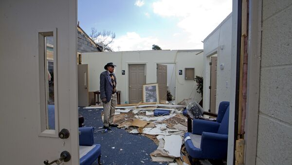 Pastor Lester Woodard surveys the damage inside Living Hope Missionary Baptist Church, Monday, April 16, 2018, in Greensboro, N.C. Sunday's tornado destroyed most of the roof and furniture in the church.  - Sputnik International