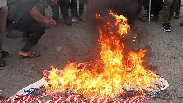 Protesters burn representations of US flags during a protest against the US-led missile attack on Syria, in Tahrir Square, Baghdad, Iraq, Sunday, April 15, 2018. - Sputnik International