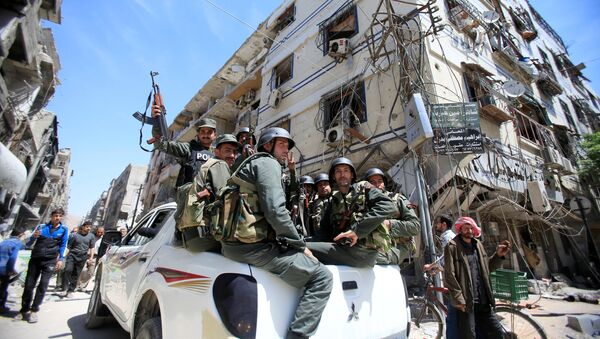 Members of the Syrian police hold their weapons as they sit on a back of a truck at the city of Douma, Damascus, Syria April 16, 2018 - Sputnik International