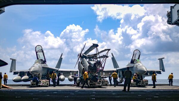 U.S. Navy sailors move aircraft from an elevator into the hangar bay of the aircraft carrier USS Theodore Roosevelt in the South China Sea April 8, 2018. Picture taken April 8, 2018 - Sputnik International