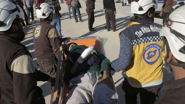 Syrian Civil Defence (known as the White Helmets) carry an injured man as Jaish al-Islam fighters and their families arrive from the former rebel bastion's main town of Douma at the Abu al-Zindeen checkpoint controlled by Turkish-backed rebel fighters near the northern Syrian town of al-Bab, on April 4, 2018 - Sputnik International