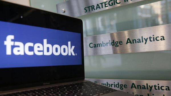 A laptop showing the Facebook logo is held alongside a Cambridge Analytica sign at the entrance to the building housing the offices of Cambridge Analytica, in central London on March 21, 2018 - Sputnik International