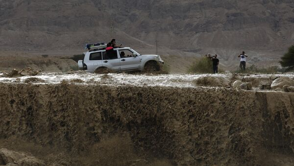 A car drives through flooded water running through a valley blocking the main road along the Dead Sea in the Judean desert, near the desert fortress of Masada north of Ein Bokek, following heavy rainfall in the mountains on April 25, 2018 - Sputnik International