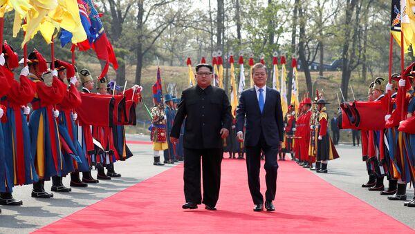 South Korean President Moon Jae-in walks with North Korean leader Kim Jong Un at the truce village of Panmunjom inside the demilitarized zone separating the two Koreas, South Korea, April 27, 2018 - Sputnik International