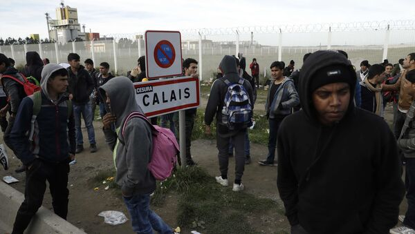 In this Thursday, Oct. 27, 2016 file photo migrants gather near a fence in Calais, northern France.  - Sputnik International