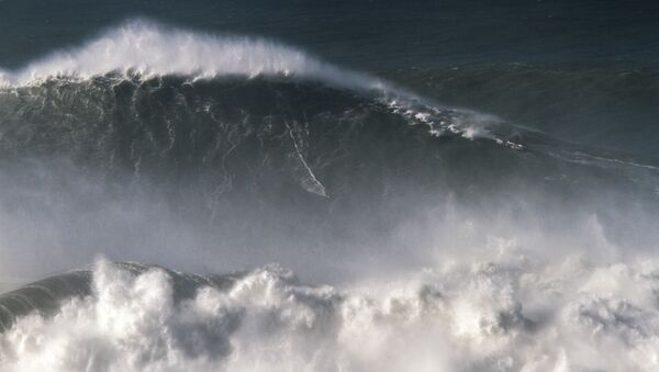 In this photo taken Nov. 8 2017, Brazilian surfer Rodrigo Koxa rides what has been judged the biggest wave ever surfed, at the Praia do Norte, or North beach, in Nazare, Portugal. On Saturday, April 28 2018, the World Surf League credited Koxa with a world record for riding the biggest wave ever surfed and said that its judging panel determined the wave was 80 feet (24.38 meters) - Sputnik International