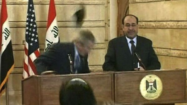 In this image from APTN video, a man throws a shoe at President George W. Bush during a news conference with Iraq Prime Minister Nouri al-Maliki on Sunday, Dec. 14, 2008, in Baghdad. The man threw two shoes at Bush, one after another. Bush ducked both throws, and neither man was hit. - Sputnik International