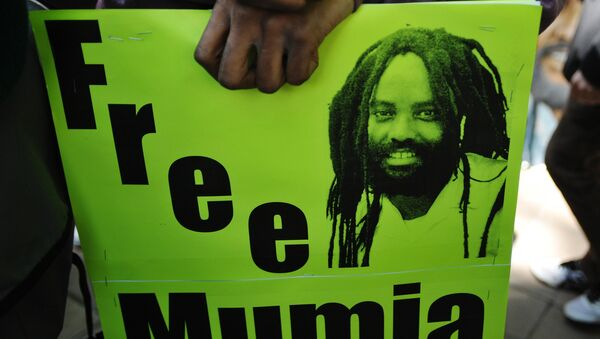 Protestors stand before an image of Mumia Abu-Jamal outside the US Department of Justice on April 24, 2012 in Washington, DC, calling for the release from prison of the ex-Black Panther militant, who was convicted for the killing of a white police officer in 1981 and sentenced to death. - Sputnik International