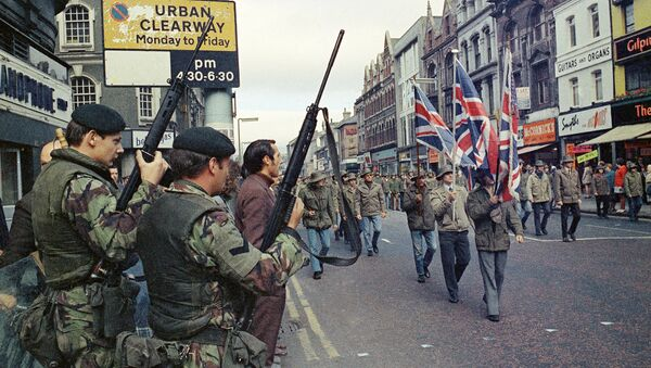 Under the watchful eyes of armed British troops, members of the Ulster Defence Association parade through Belfast, Northern Ireland in August 1972 - Sputnik International