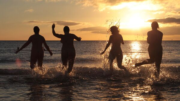 Nudists take part in the annual North East Skinny Dip as the sun rises at Druridge Bay in Northumberland, northeast England on September 22, 2013 - Sputnik International