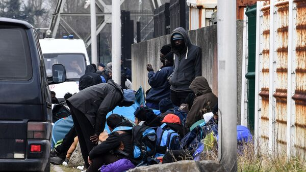 Migrants gather by the ringroad leading to the harbour on March 30, 2018 in Calais, near a police van patrolling (Rear L) - Sputnik International
