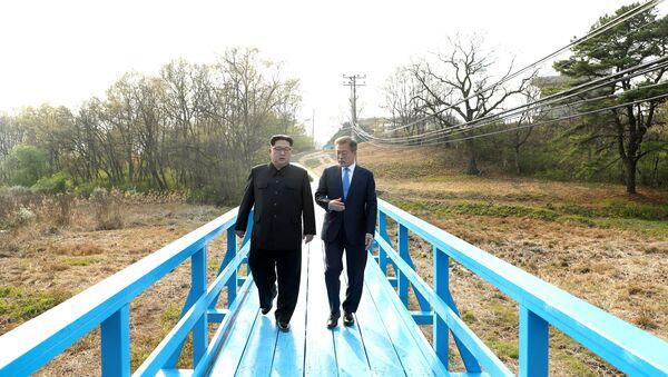 South Korean President Moon Jae-in and North Korean leader Kim Jong Un walk together at the truce village of Panmunjom inside the demilitarized zone separating the two Koreas, South Korea, April 27, 2018 - Sputnik International