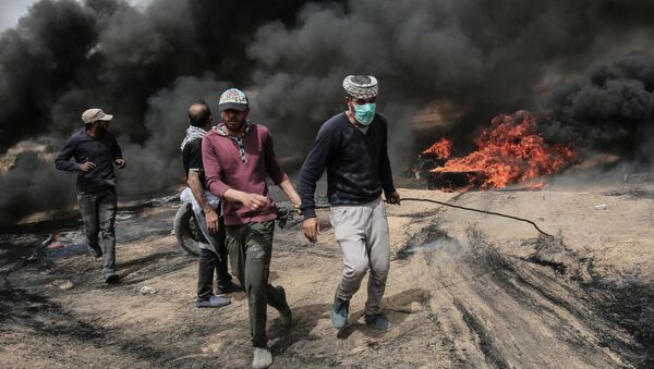 Palestinian protesters pull on a burning tire during clashes with Israeli forces on April 20, 2018, east of Khan Yunis, in the southern Gaza Strip during mass protests along the border of the Palestinian enclave, dubbed The Great March of Return, which has the backing of Gaza's Islamist rulers Hamas - Sputnik International
