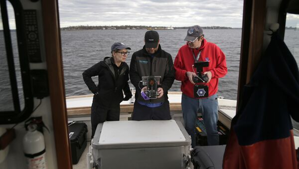 In this April 29, 2018, photo, artist Melinda Hunt, president of The Hart Island Project, left, and drone operator Parker Gyokeres, right, look over the footage recorded by Daniel Herbert from the drone flight over Hart Island in New York - Sputnik International