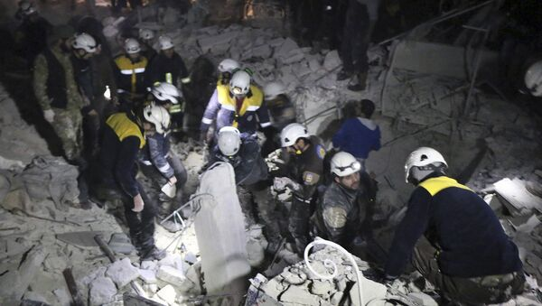 This photo provided on Sunday, Jan. 7, 2018 by the Syrian Civil Defense White Helmets, which has been authenticated based on its contents and other AP reporting, shows Civil Defense workers inspecting a damages building after a bombing that targeted the office of Ajnad al-Koukaz, a militant group consisting of foreign fighters mostly from the Caucuses and Russia, in Idlib, Syria - Sputnik International