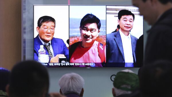 People watch a TV news report on screen, showing portraits of three Americans, Kim Dong Chul, left, Tony Kim and Kim Hak Song, right, detained in the North Korea at the Seoul Railway Station in Seoul, South Korea, Thursday, May 3, 2018. - Sputnik International