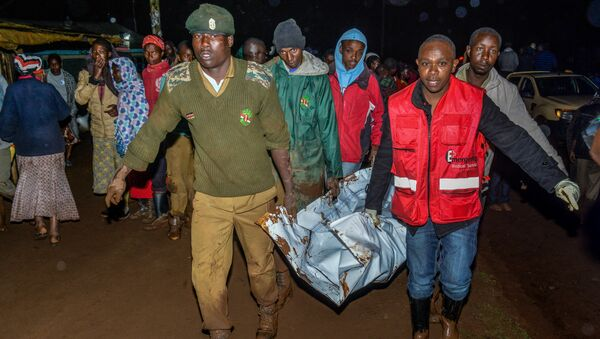 People carry a victim's body from a residential area after Patel dam burst its bank at Solai, about 40 kilometres north of Nakuru, Kenya, on May 10, 2018 - Sputnik International