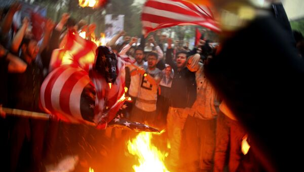 Iranian demonstrators burn representations of the U.S. flag during a protest in front of the former U.S. Embassy in response to President Donald Trump's decision Tuesday to pull out of the nuclear deal and renew sanctions, in Tehran, Iran, Wednesday, May 9, 2018 - Sputnik International