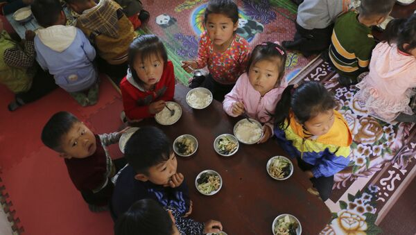 In this May 9, 2018 photo provided by the World Food Program (WFP), children eat a meal at a nursery and kindergarten where WFP provides food assistance in Sinwon county in North Korea's South Hwanghae province - Sputnik International