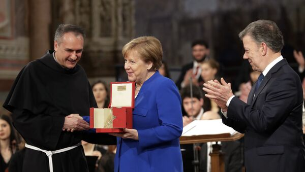 German Chancellor Angela Merkel, center, flanked by Colombian President Juan Manuel Santos, right, receives the St. Francis lamp peace prize by Father Mauro Gambetti during a ceremony inside Assisi's Basilica, Italy, Saturday, May 12, 2018 - Sputnik International
