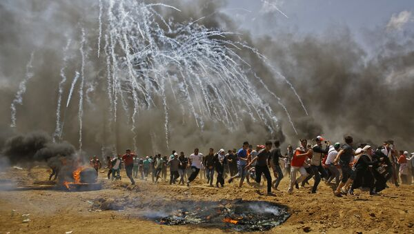Palestinians run for cover from tear gas during clashes with Israeli security forces near the border between Israel and the Gaza Strip, east of Jabalia on May 14, 2018, as Palestinians protest over the inauguration of the US embassy following its controversial move to Jerusalem - Sputnik International