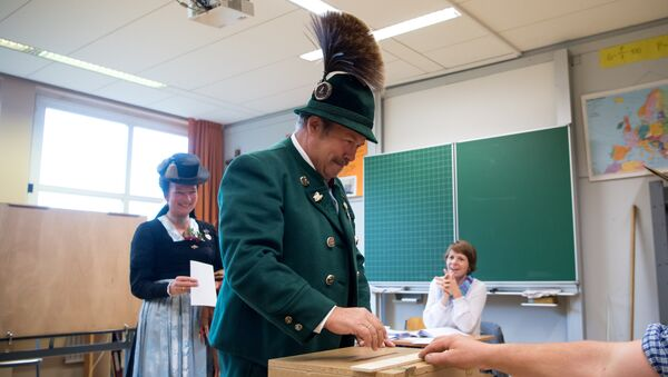 A man and a woman in traditional Bavarian dresses cast their ballots at a polling station in Unterwoessen near Rosenheim, southern Germany, during general elections on September 24, 2017 - Sputnik International