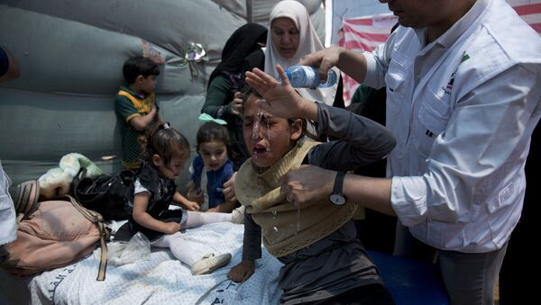 Medics treat Palestinian children suffering from teargas inhalation during a protest near Beit Lahiya, Gaza Strip, Monday, May 14, 2018 - Sputnik International