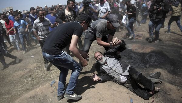 An elderly Palestinian man falls on the ground after being shot by Israeli troops during a deadly protest at the Gaza Strip's border with Israel, east of Khan Younis, Gaza Strip, Monday, May 14, 2018 - Sputnik International