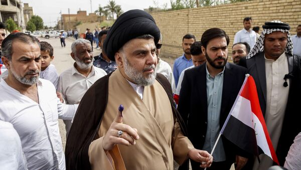 Iraqi Shiite cleric and leader Moqtada al-Sadr (C-L) shows his ink-stained index finger and holds a national flag while surrounded by people outside a polling station in the central holy city of Najaf on May 12, 2018 as the country votes in the first parliamentary election since declaring victory over the Islamic State (IS) group - Sputnik International
